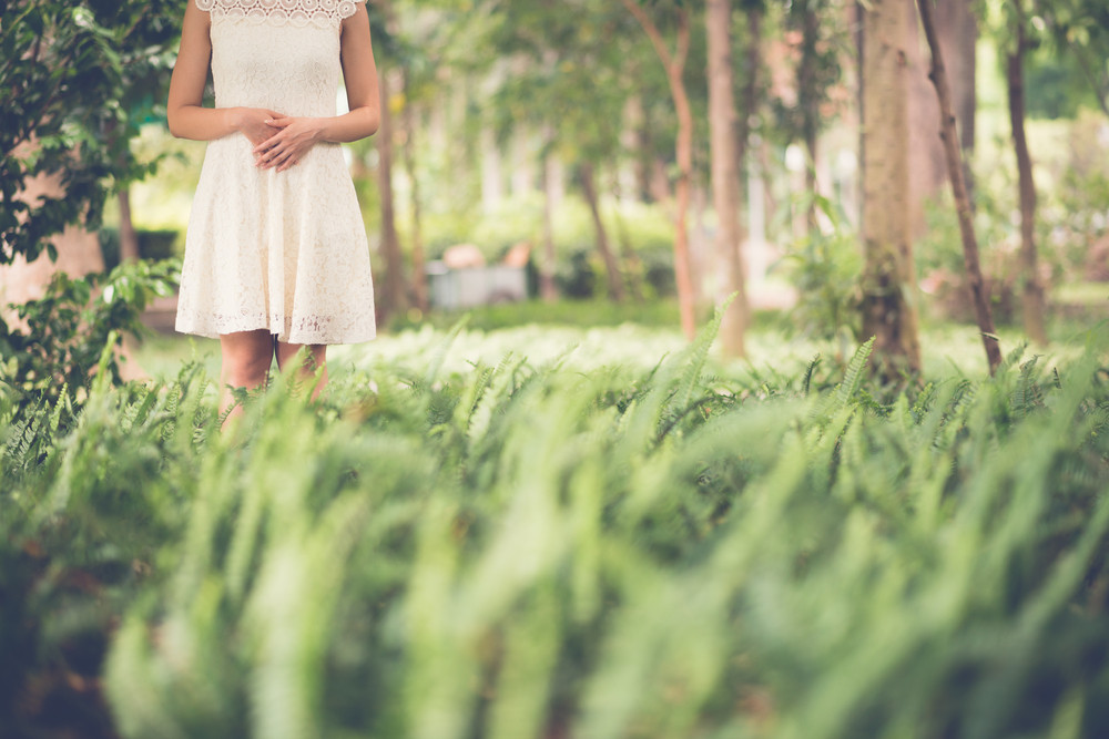 Mulher irreconhecível de pé na floresta