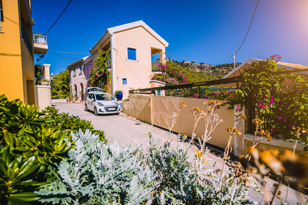 Vacation travel with car concept. Rental hired car in the narrow picturesque street of small greek town. Discover Mediterranean Islands. Summer time holiday trip