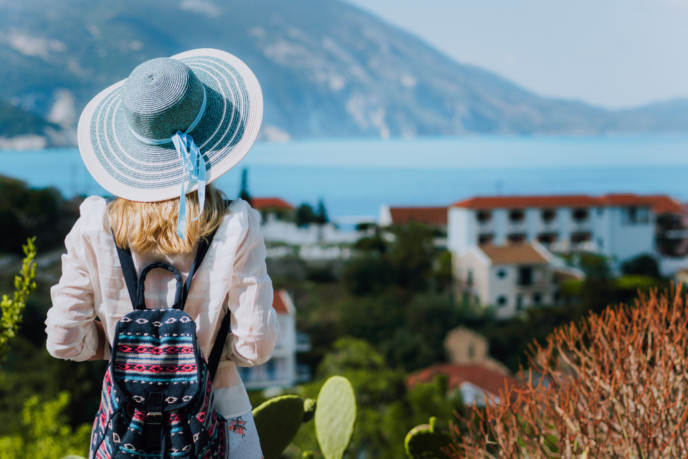 Vintage photo of tourist female with blue sun hat and travel backpack enjoying panorama of colorful small Assos village. Kefalonia, Greece
