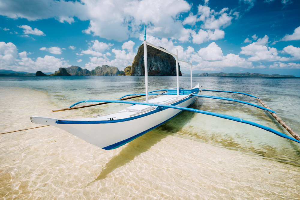 White Banca Boat On The Sandy Beach Ready For Island Hopping