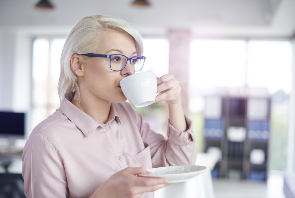 Woman drinking coffe at office