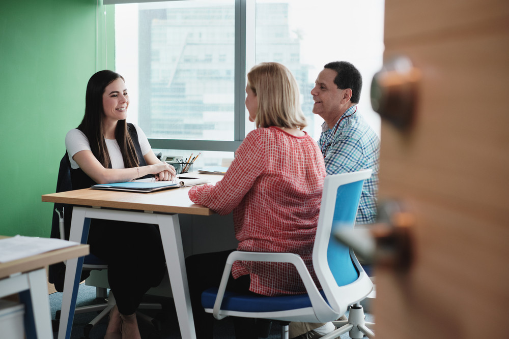 Woman working as advisor with old couple or financial consultant talking to elderly people. Senior husband and wife meeting health insurance broker or retirement plan agent in office