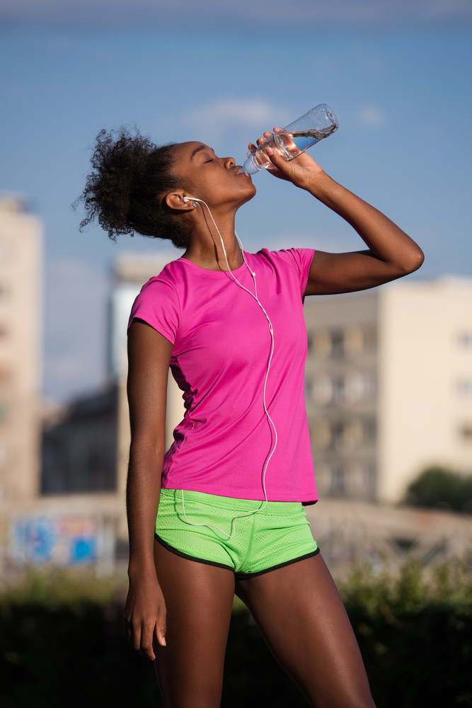 Young beautiful african american woman with headphones drinking water after jogging in the city