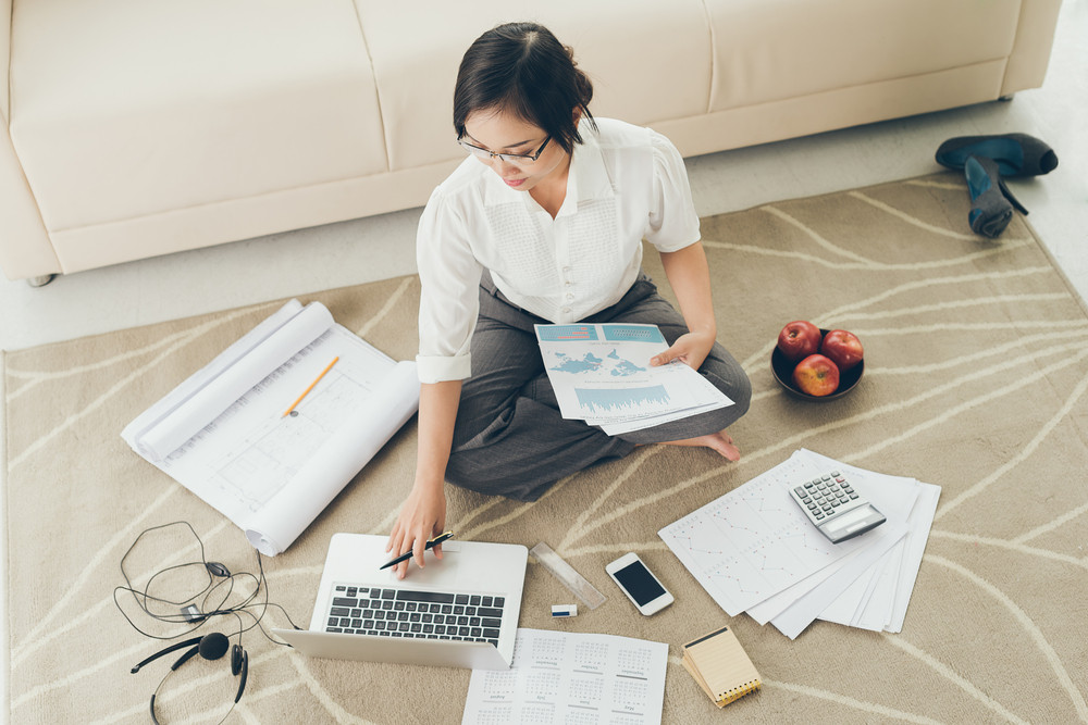 Young business woman working with papers while sitting on the floor at home
