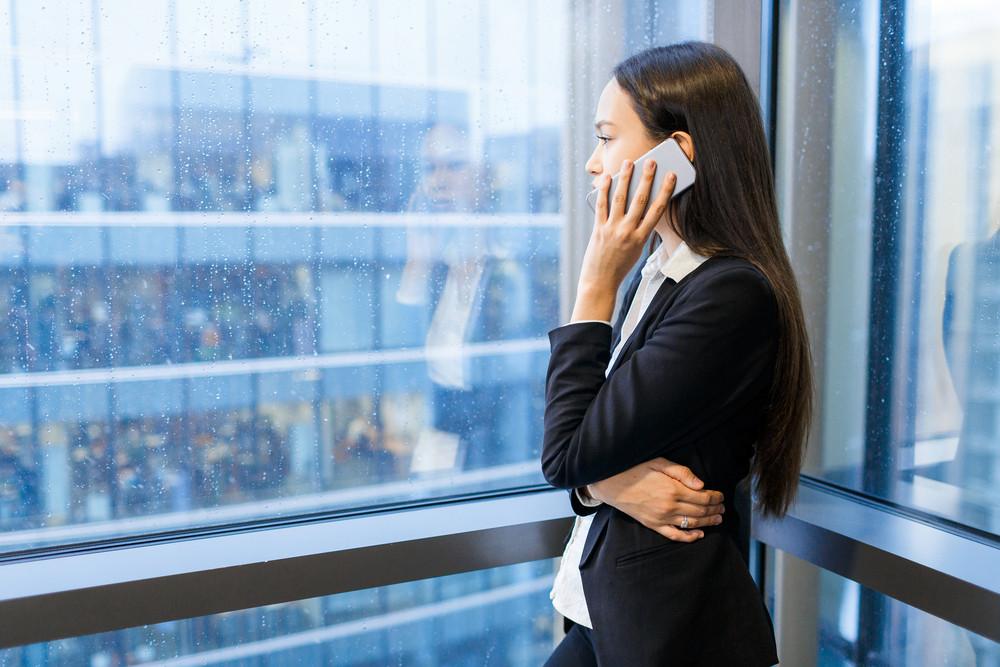 Young female in formalwear speaking on cellphone by window