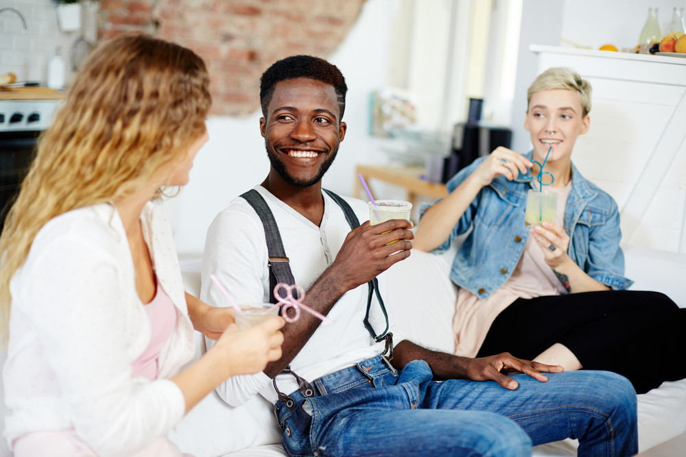 Young man and two girls with drinks having talk at leisure