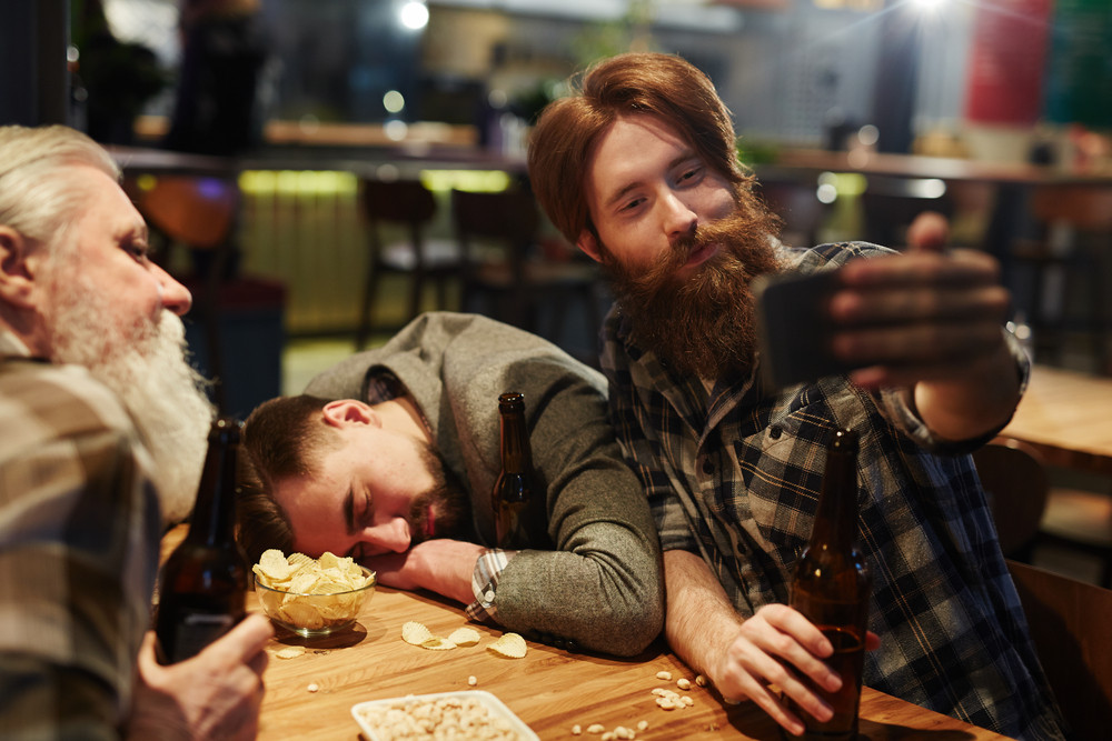 Young man with bottle of beer making selfie in pub