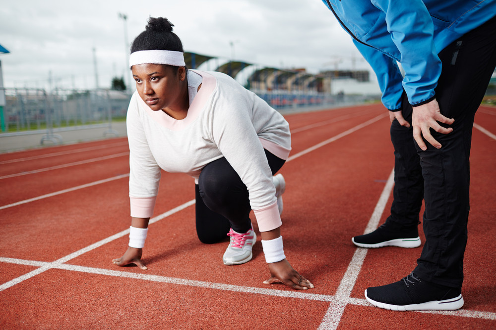 Young oversized sporty woman standing by start line ready to run with her trainer near by