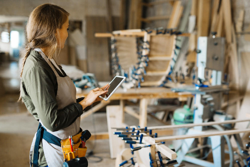 Young owner of woodwork workshop searching for necessary data in the net