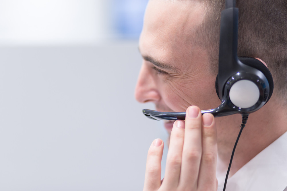 young smiling male call centre operator doing his job with a headset