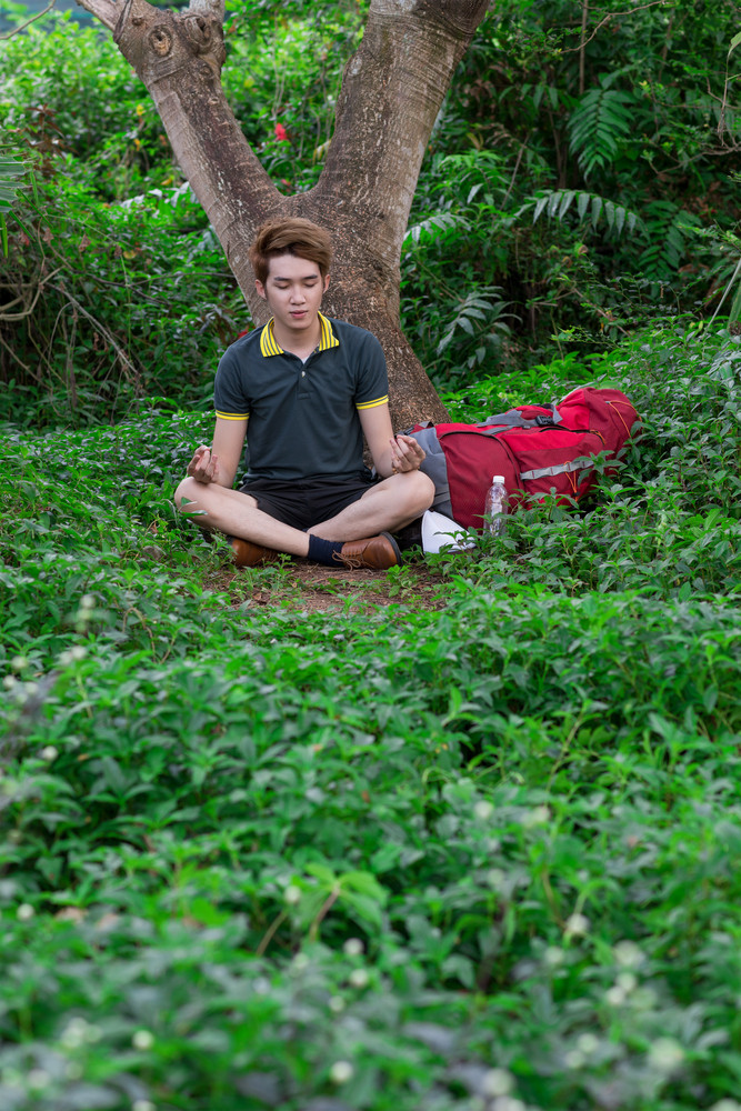 Young tourist meditating in the forest