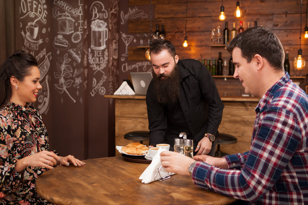 Young waiter serving food to male and female customers at table in cafe. Hipster pub.