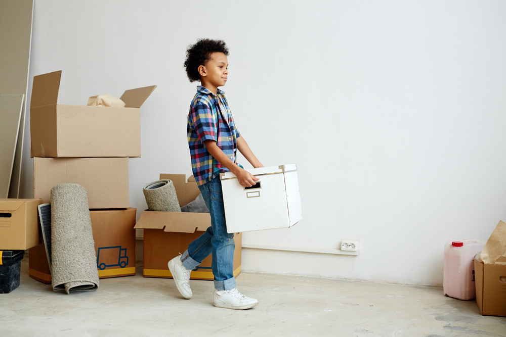 Youngster with packed box moving in new flat