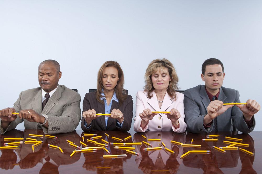Stressed people breaking pencils in office