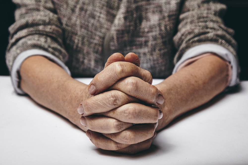 Studio photography of praying hands of a senior woman on table. Old hands clasped on a table.