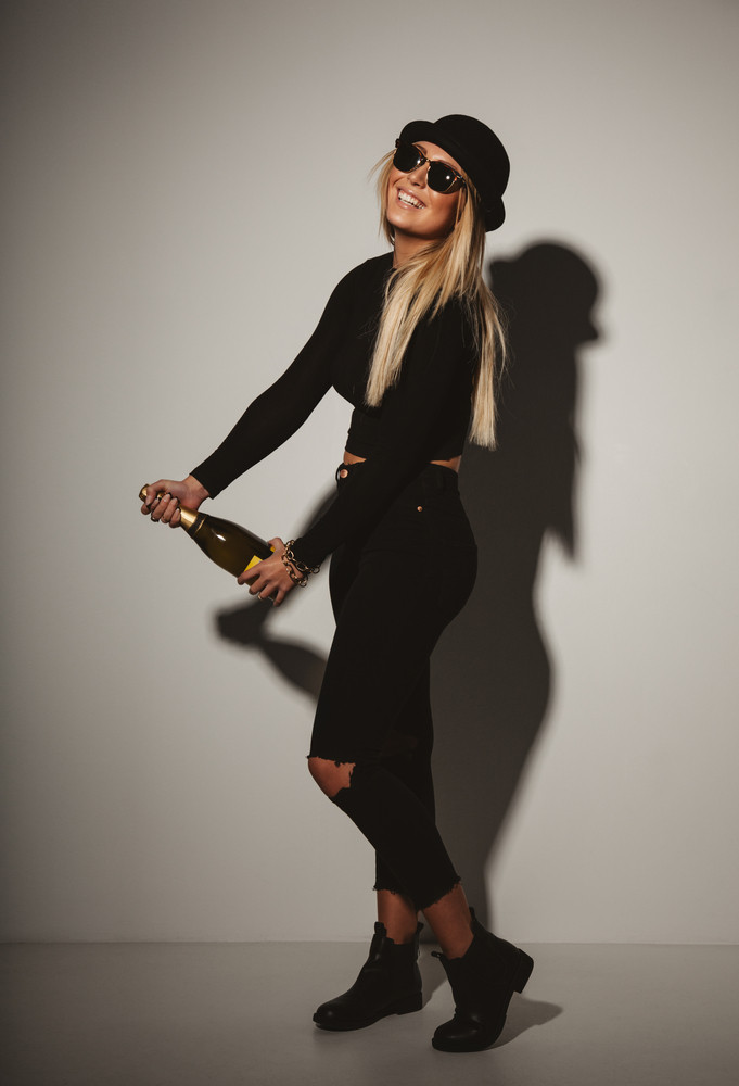 Studio shot happy young woman wearing hat and sunglasses celebrating success with a champagne.