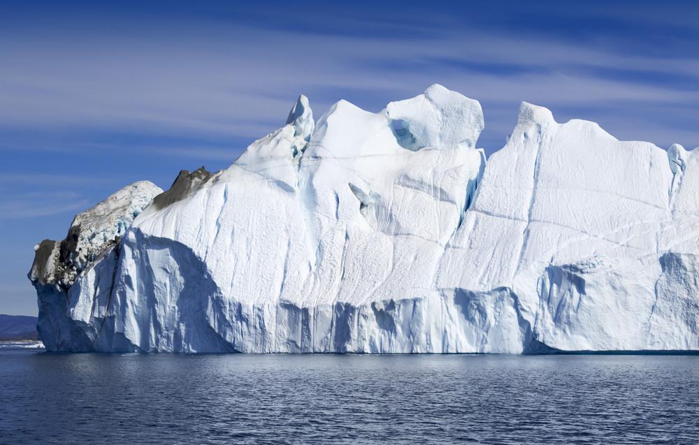 Sunlit, dirt-streaked iceberg in deep blue water
