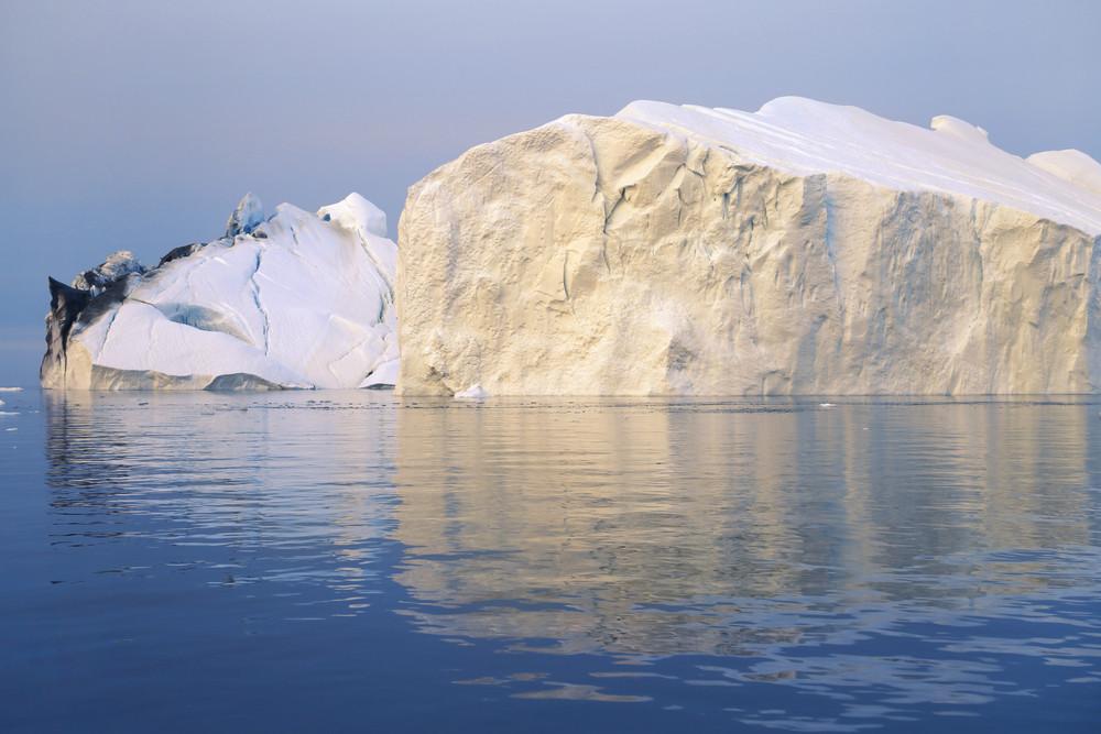 Sunlit iceberg streaked with dirt in deep blue water