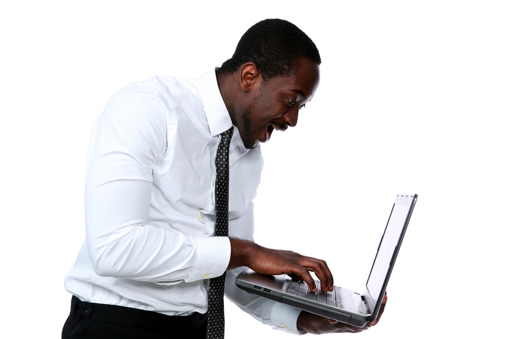 Surprised african man standing and using laptop over white background