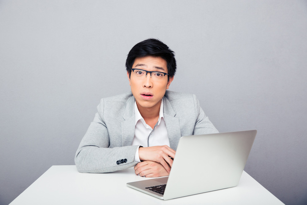Surprised businessman sitting at the table with laptop
