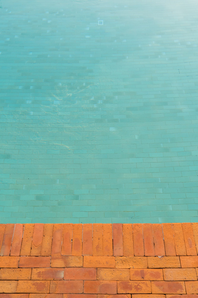 Swimming pool background brick floor and green water.