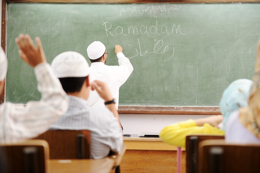 Teacher at classroom writing Ramadan on board