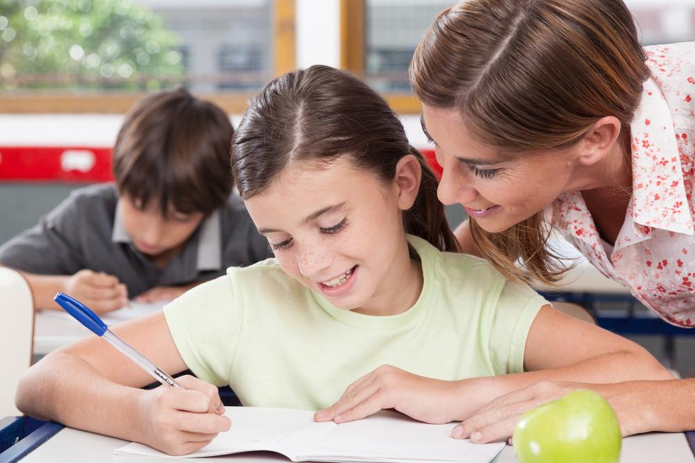 teacher helping a girl in the classroom