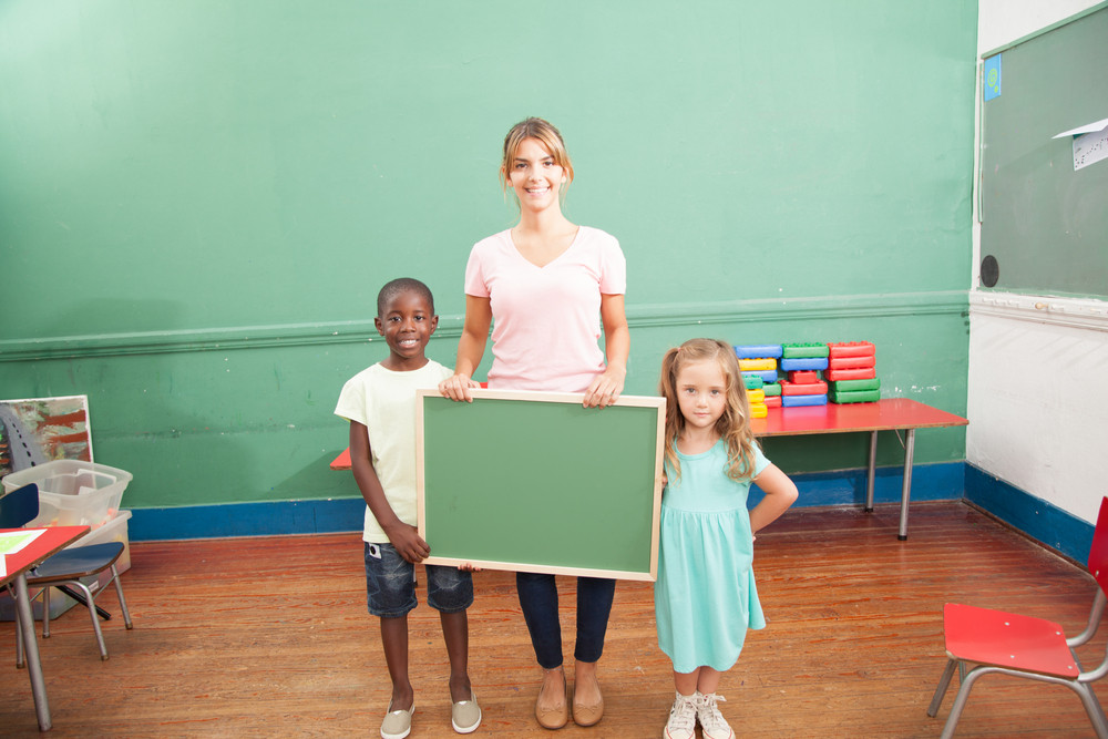 Teacher with her students holding a blackboard