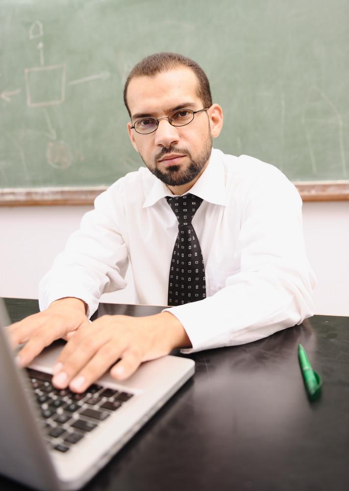 Teacher with laptop at school classroom