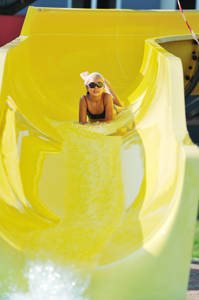 Girl have fun on water slide at outdoor swimming pool