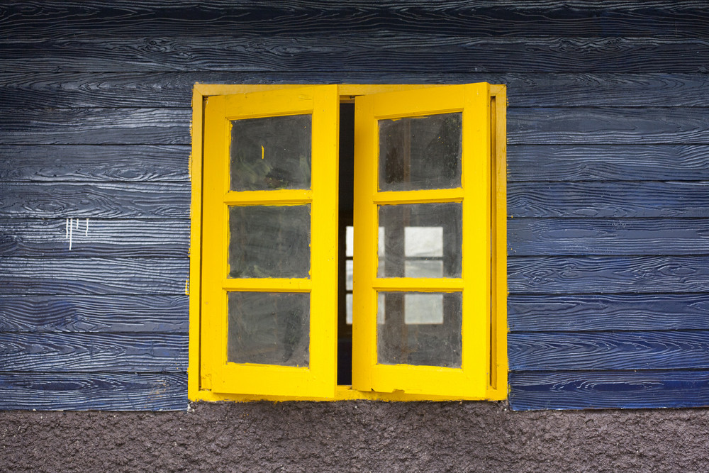 Texture of bright painted wooden wall with yellow closed window
