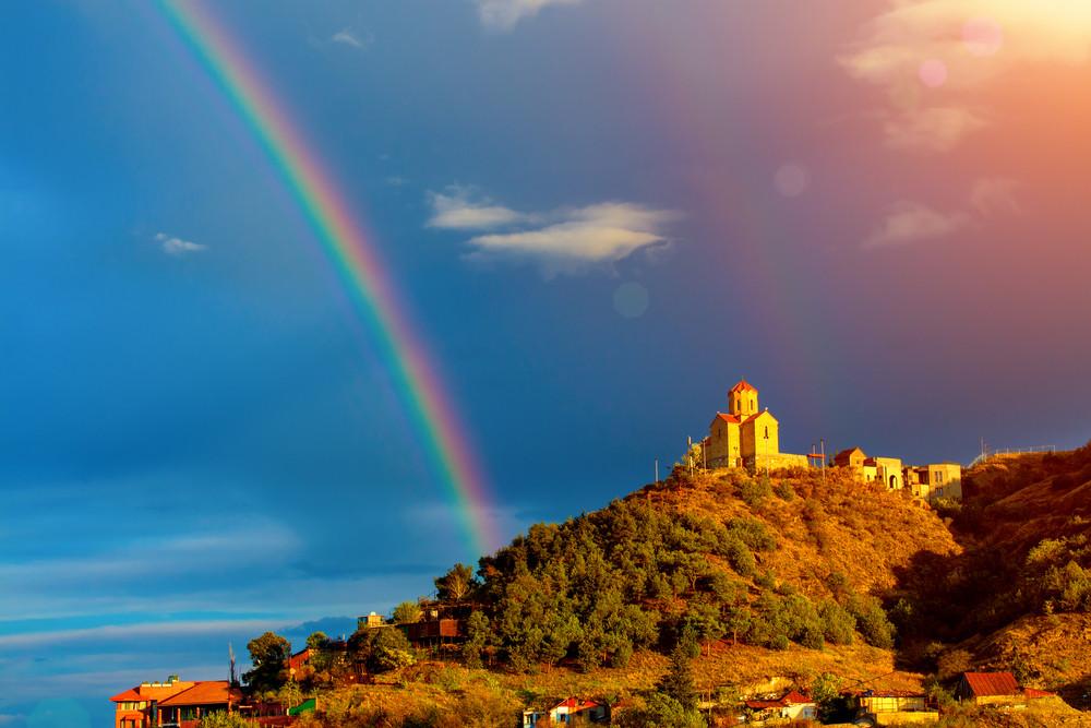 Mosteiro de Thabori em uma colina com arco-íris atrás em Tbilisi