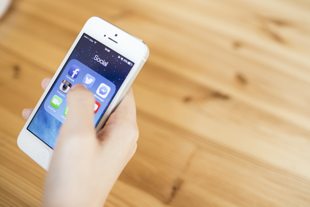 THAILAND - SEPTEMBER 07, 2014: All of popular social media icons on smartphone device screen with hand holding.