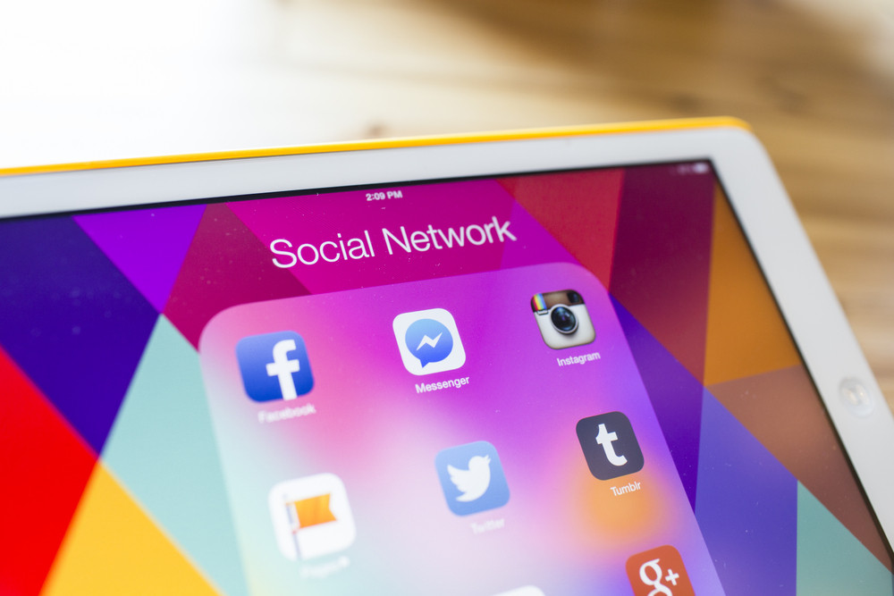THAILAND - SEPTEMBER 07, 2014: All of popular social media icons on tablet device screen wood background.