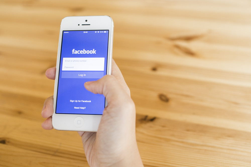 THAILAND - SEPTEMBER 07, 2014: Facebook page sign in page first landing homepage view on application smartphone hand holding.