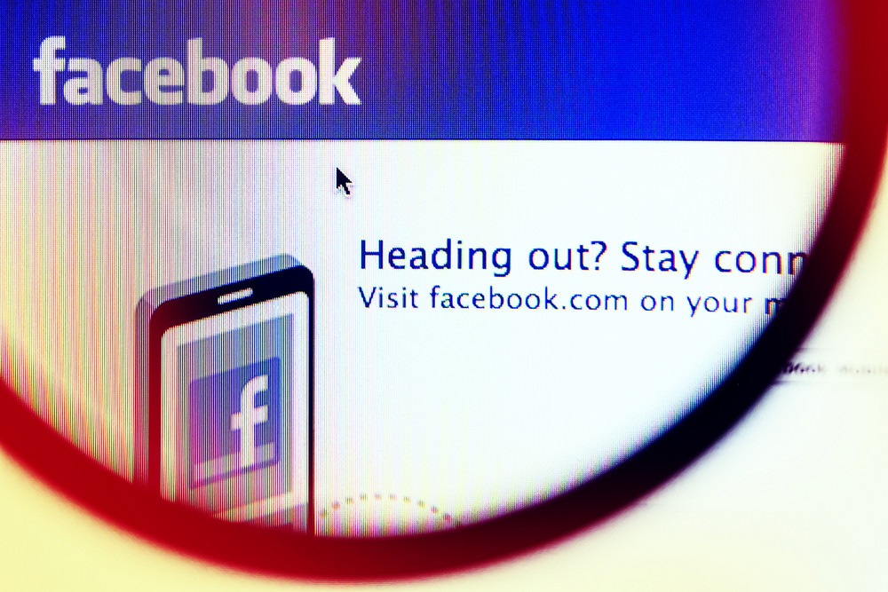 THAILAND - SEPTEMBER 2, 2014: Magnifying glass of Facebook page view on web browser.