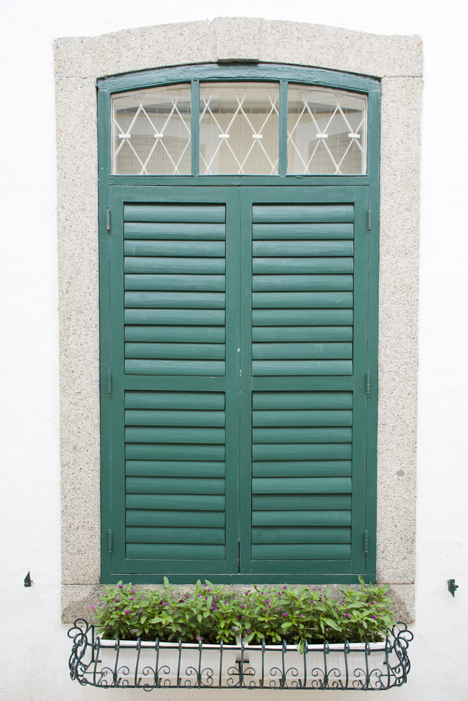 the closed green window on the white wall