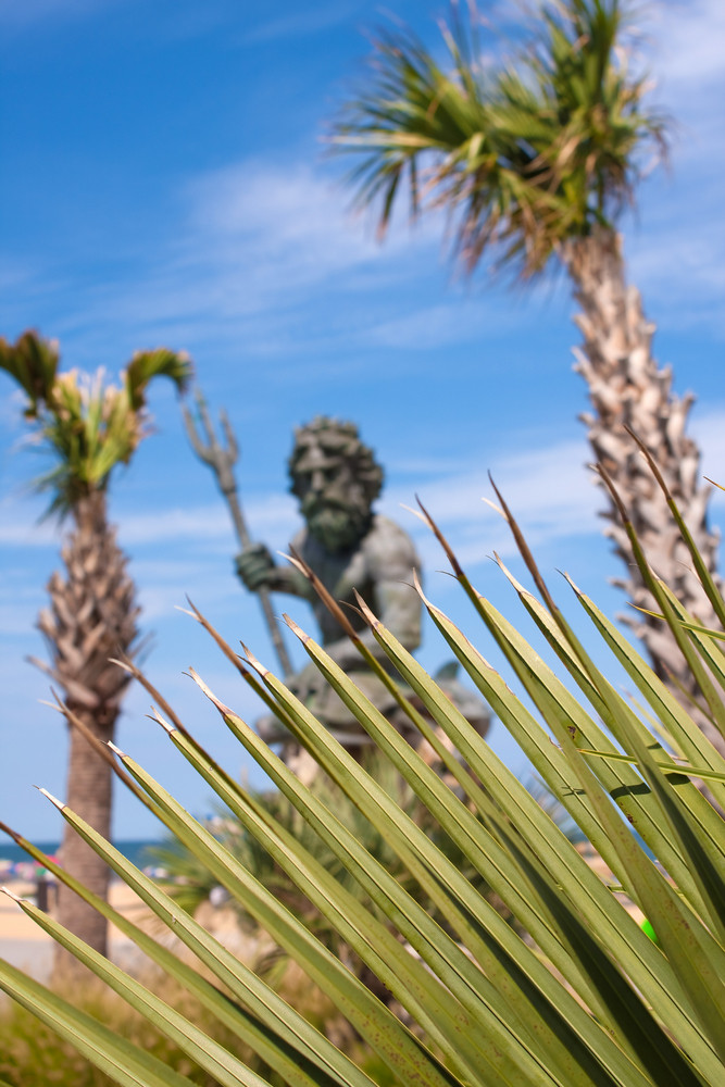 The large public statue of King Neptune in Virginia Beach.  Shallow depth of field with sharp focus on the green tropical foliage.
