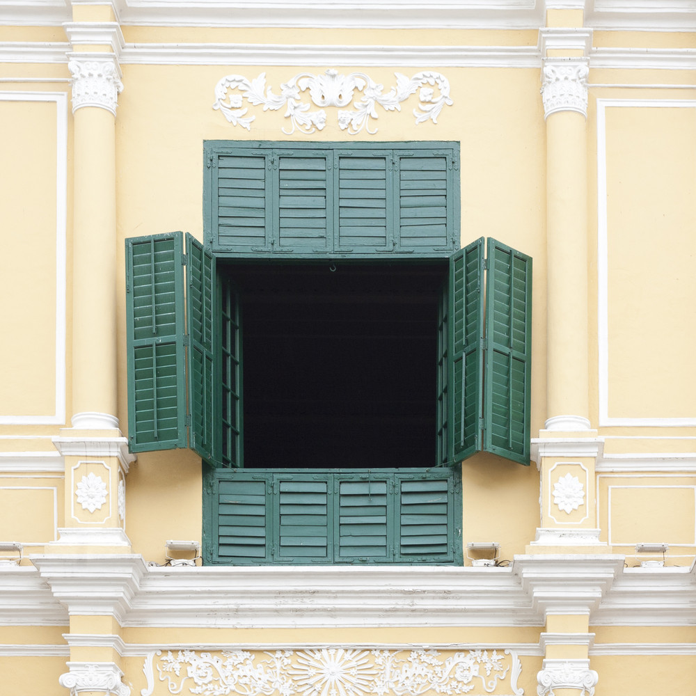 the opened green window on the yellow wall
