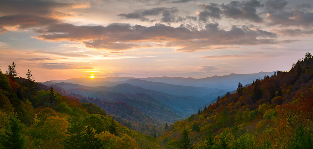 The sun rises over the mountains during autumn.