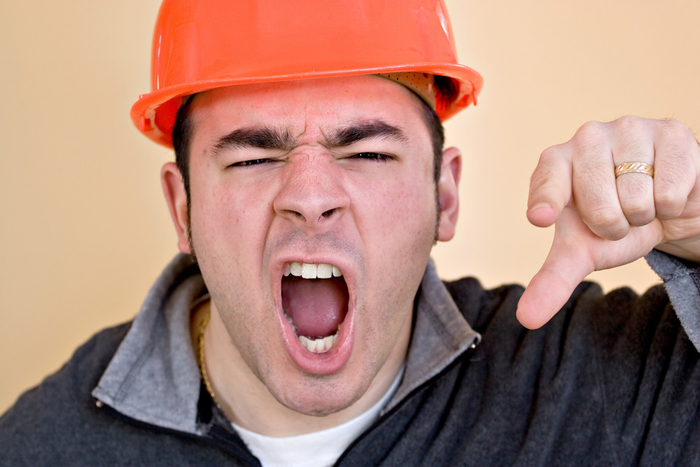 This construction worker is pointing and yelling his head off at someone.