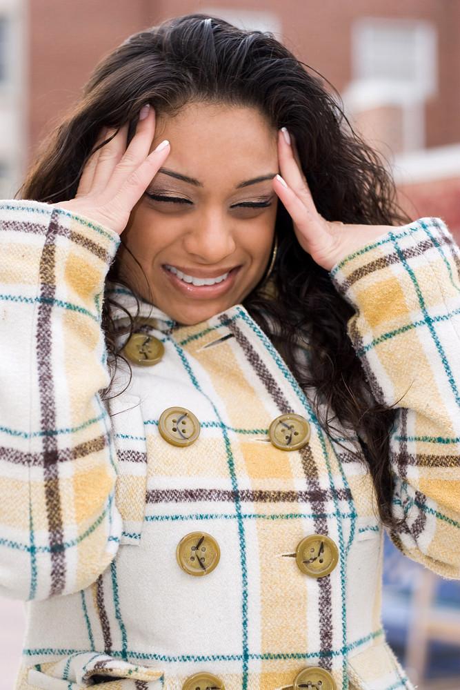 This woman is experiencing an intense headache.