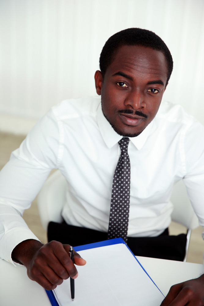 Thoughtful african man sitting at the table and signing document in office