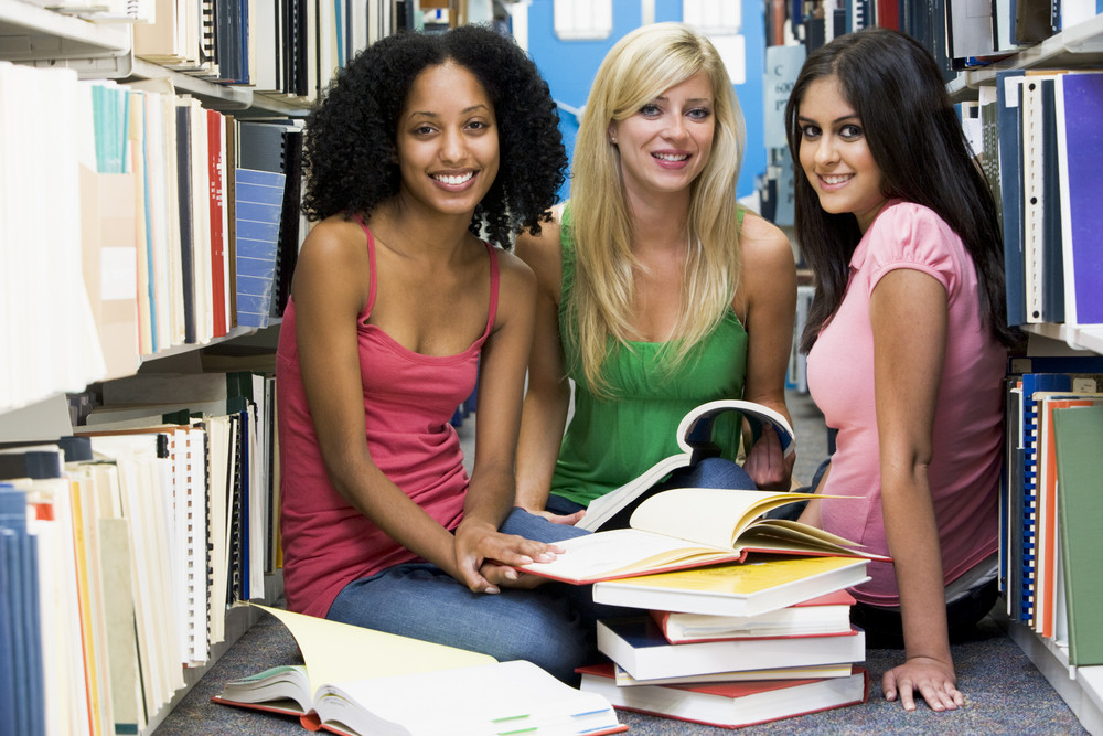 Three female students sitting on floor of library surrounded by books