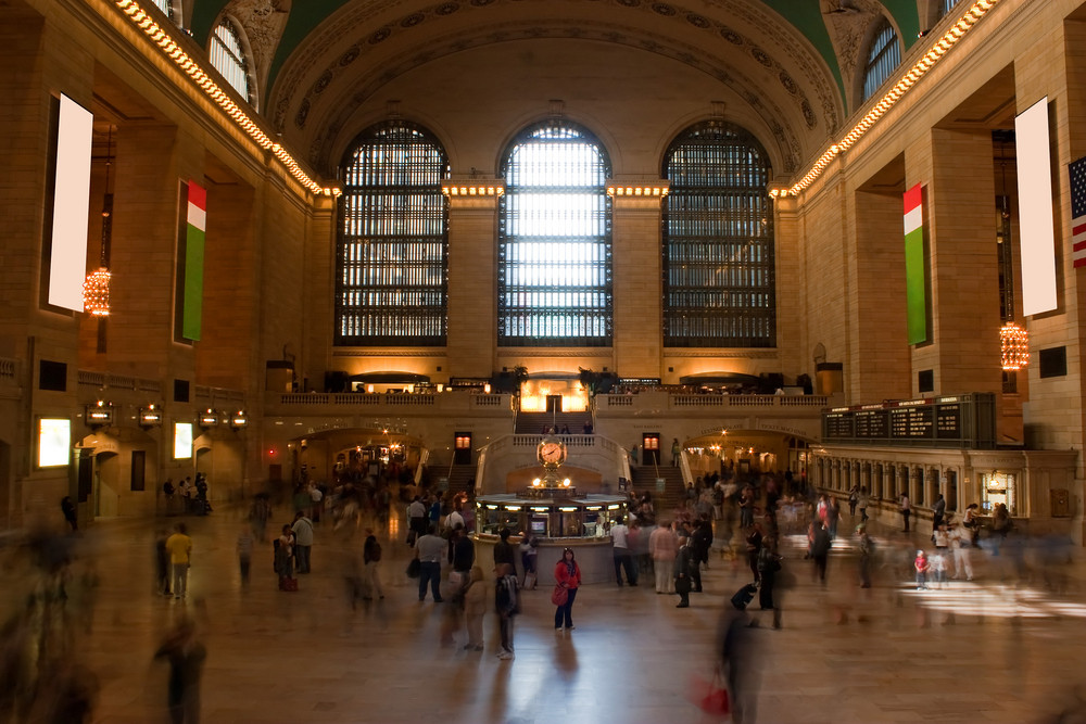 Time lapse photo of blurred people walking through Grand Central Terminal train station in New York City with one recognizable woman standing alone in the center.