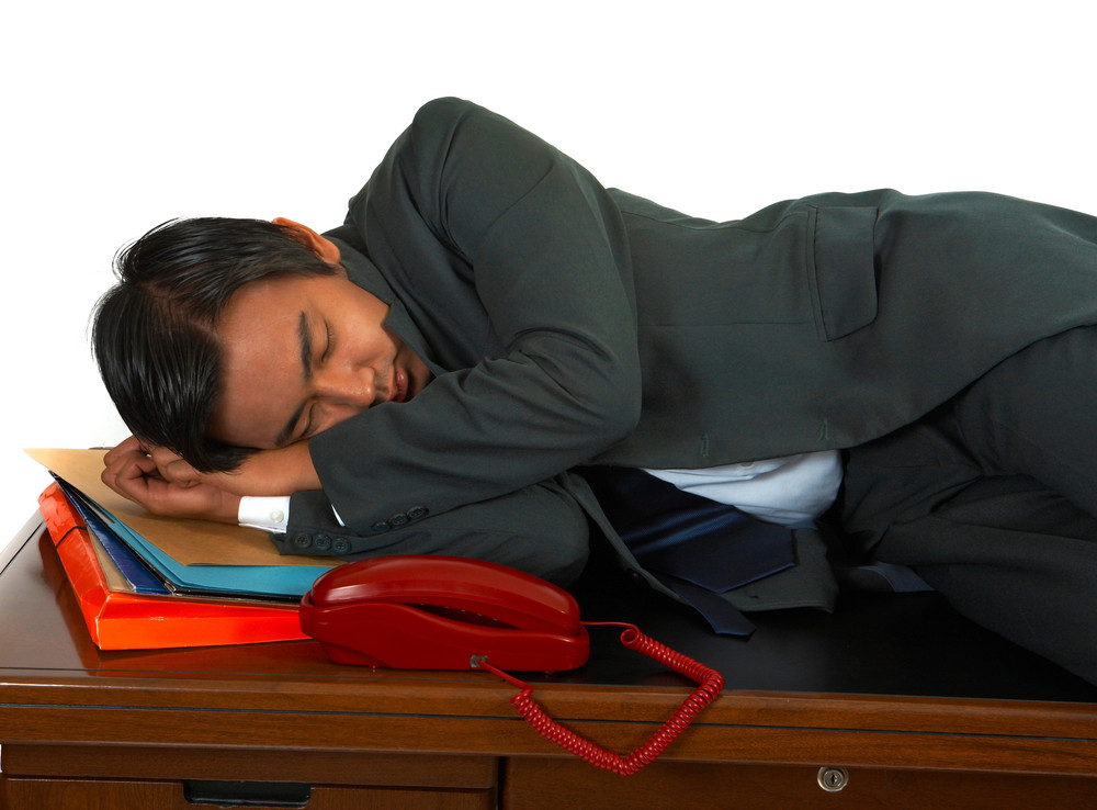 Tired Businessman Lying On His Desk