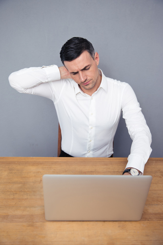Tired businessman sitting at the table with laptop