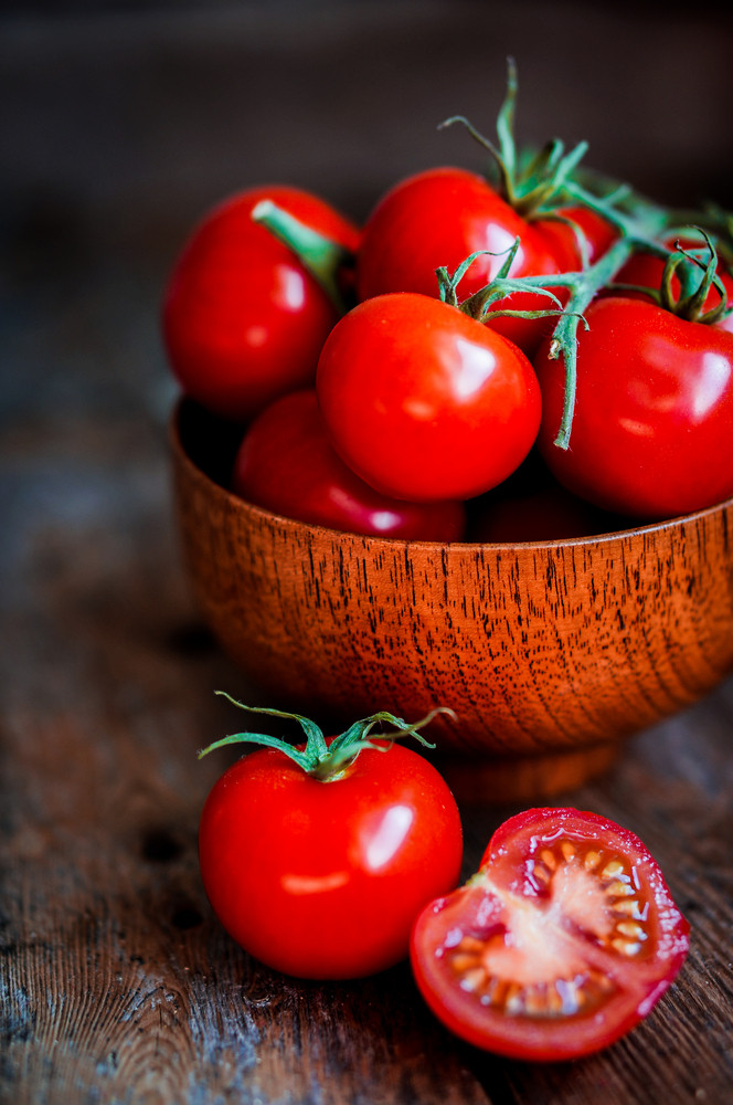 Tomatoes In The Basket On Wooden Background