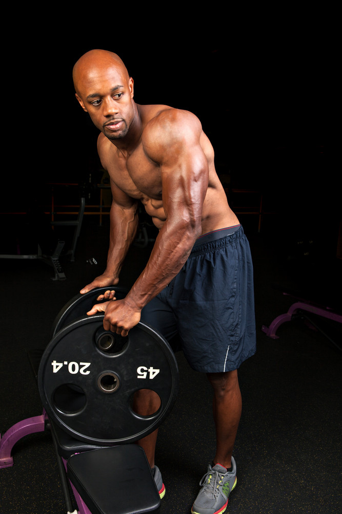 Toned and ripped lean muscle fitness man lifting plate weights.