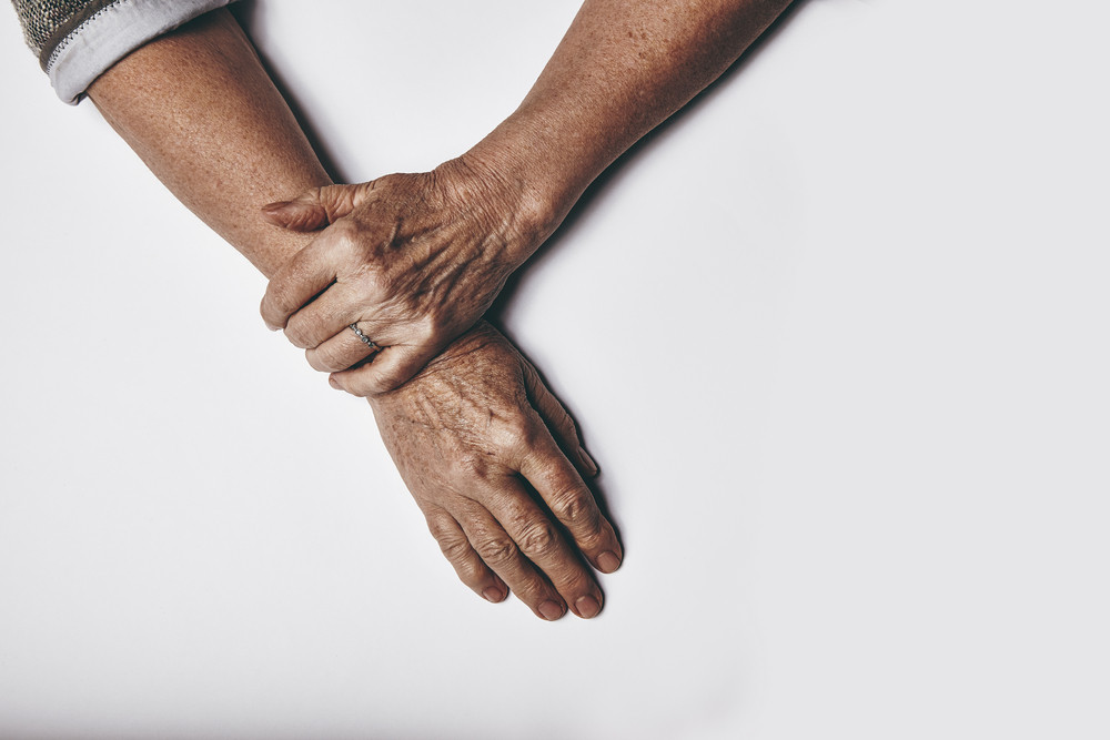 Top view of an elderly woman's hands resting on grey background. Relaxed old female hands together.